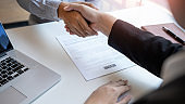 Business Meeting agreement Handshake concept, Hand holding after finishing up dealing project or bargain success at negotiation over office background