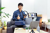 Young asian male blogger recording vlog video on camera review of product at home office, Focus on tripod mounted camera screen broadcast live stream video to a social network