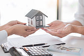 Sale representative offer house purchase contract to buy a house or apartment or discussing about loans and interest rates