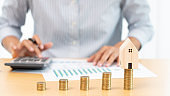 Property investment and house mortgage financial concept, hand of a businessman who is stacking coins for Real estate investment, saving for buying for housing or speculation