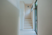 Building interior in light colours with staircase, glass wall and geometric shapes