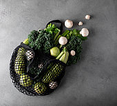 green vegetables and fruits in an eco bag on a gray table
