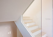 Apartment interior in light colours with staircase, glass wall and geometric shapes
