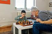 Grandpa and grandchild playing board game