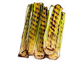 Grilled baby leeks isolated on white