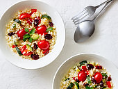 Couscous salad with tomatoes, peppers, courgettes and cranberries. Vegetarian food. Diet. Healthy eating.