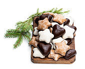 Sugar and chocolate glazed seasonal spiced cookies on wooden cutting board isolated on white