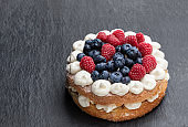 Victoria sponge cake with whipped cream and berries on top on black stone background