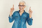 Studio shot of Senior Woman Pointing Away