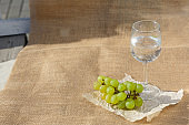 Still life and food photo. A bunch of grapes, a glass of water stand on burlap on a wooden floor