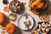 Fall thanksgiving table with roasting chicken or turkey, nuts, pie, pumkins and other food on light