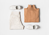 Fashion flat lay with beige caramel casual cozy sweater, white jeans and sneakers on white background