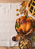 Fall thanksgiving table with roasting chicken or turkey, nuts, pie, pumkins and other food on light tablecloth