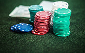 Casino poker chips stack with playing cards, dice and money on green felt background