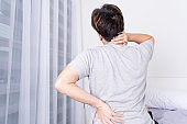 Young man suffering neck and back pain from uncomfortable bed. Healthcare medical or daily life concept.