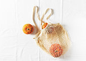Zero waste flat lay with mesh bag and autumn vegetables pumpkin