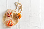 Zero waste flat lay with mesh bag and autumn vegetables pumpkin and apples on white background