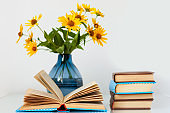 Cozy home interior decor: stack of books and vase with yellow flowers on a table. Distance home education.Quarantine concept of stay home