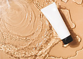 Tuba of cream cosmetic in clean transparent water with sunlight on beige background