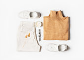 Fashion flat lay with beige, caramel sweater casual fall or winter look with sneakers, lipstick and pampas grass on white background