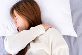 Young woman suffering neck and shoulder pain from uncomfortable bed. Healthcare medical or daily life concept.