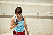 Young Hispanic women sending a text message on a smart phone and dressed in sports clothing.