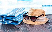 Vintage summer wicker straw beach hat, sun glasses, blue towel near swimming pool, tropical background