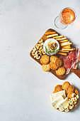 Wooden board with cheese, ham, bread stick, nut cashew, walnut and honey on camembert  on white background