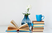 Cozy home interior decor: stack of books, cup of coffee and vase with white flower on a glass table. Distance home education.Quarantine concept of stay home