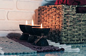 Burning spa aroma candle in coconut shell on a knitted multicolored rug and wicker box with a towel opposite the white wall, cozy home interior