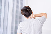 Young man suffering neck and shoulder pain from uncomfortable bed. Healthcare medical or daily life concept.