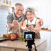 Couple senior Asian elder happy living in home kitchen. Grandfather and grandmother wiping bread with jam vlog vdo for social blogger. Focus on camera. Modern lifestyle & relationship.