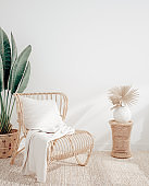 Living room interior with wicker armchair and flower, white wall mock up background