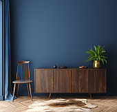 Commode with chair and decor in living room interior, dark blue wall mock up background
