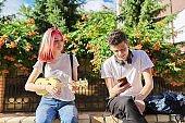 Couple of teenage hipsters outdoor, girl playing ukulele