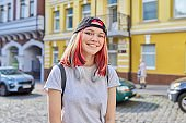 Portrait of fashionable hipster teenage girl with colored dyed hair in black cap