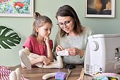 Mother and daughter child together sewing toy hare