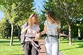 Two beautiful happy girls teenagers 17, 18 years old walking together in park