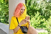 Fashionable teenager girl with colored dyed hair with a smartphone outdoors.