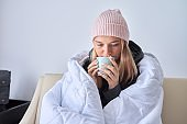 Cold autumn winter season, teenage girl sitting on sofa under warm blanket