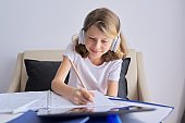 Child with digital tablet and headphones writing in notebook
