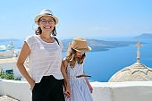 Mother and daughter child walking together on famous tourist island of Santorini