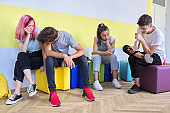 Group of teenage students at school sitting resting talking