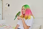 Trendy with colored hair teenager girl with green parrot on hand
