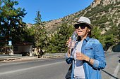 Beautiful mature woman standing on mountain road drinking water from bottle