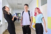 Group of teenage students talking to a female teacher in school corridor