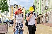 Trendy teenage hipsters boy and girl walking talking on city street