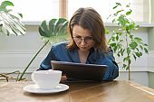 Serious mature woman having breakfast at home reading digital tablet
