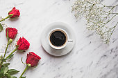 Roses and coffee flat lay on marble table