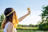 Teenager girl with hippie hairstyle holding dry dandelions in her hand